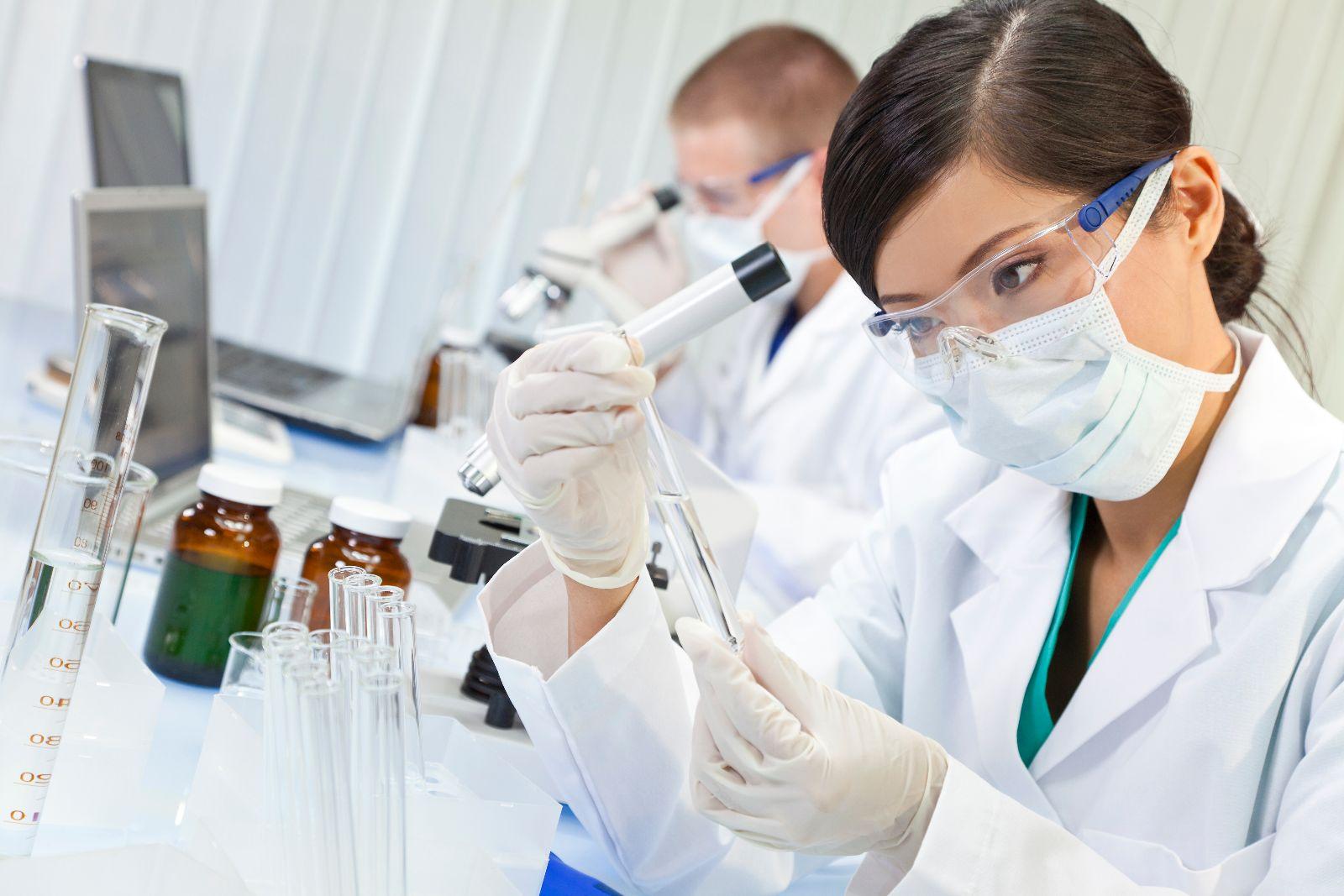 Mujer observando tubo de ensayo en el fondo un laboratorio