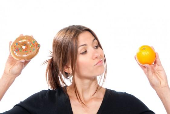 Mujer con camis negr sostenidno en la mano derecha una dona y en la izquierda una naranja
