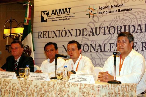 """Personas que representan autoriadades sanitarias sentadas en el fondo un anuncio con el lema """"reunión de autoridades nacionales de América Latina """""""