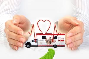 Ambulancia entre manos con un simbolo de corazón