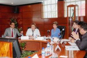 Mercedes Juan y funcionarios de la Red Mexicana de Municipios sentados en una mesa de madera atrás un muro de madera