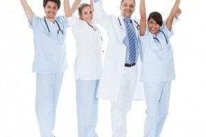 Médicos con los brazos en alto y sonriendo