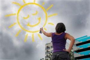Concepto de optimismo mujer pintando un sol brillante sobre el cielo un cielo obscuro