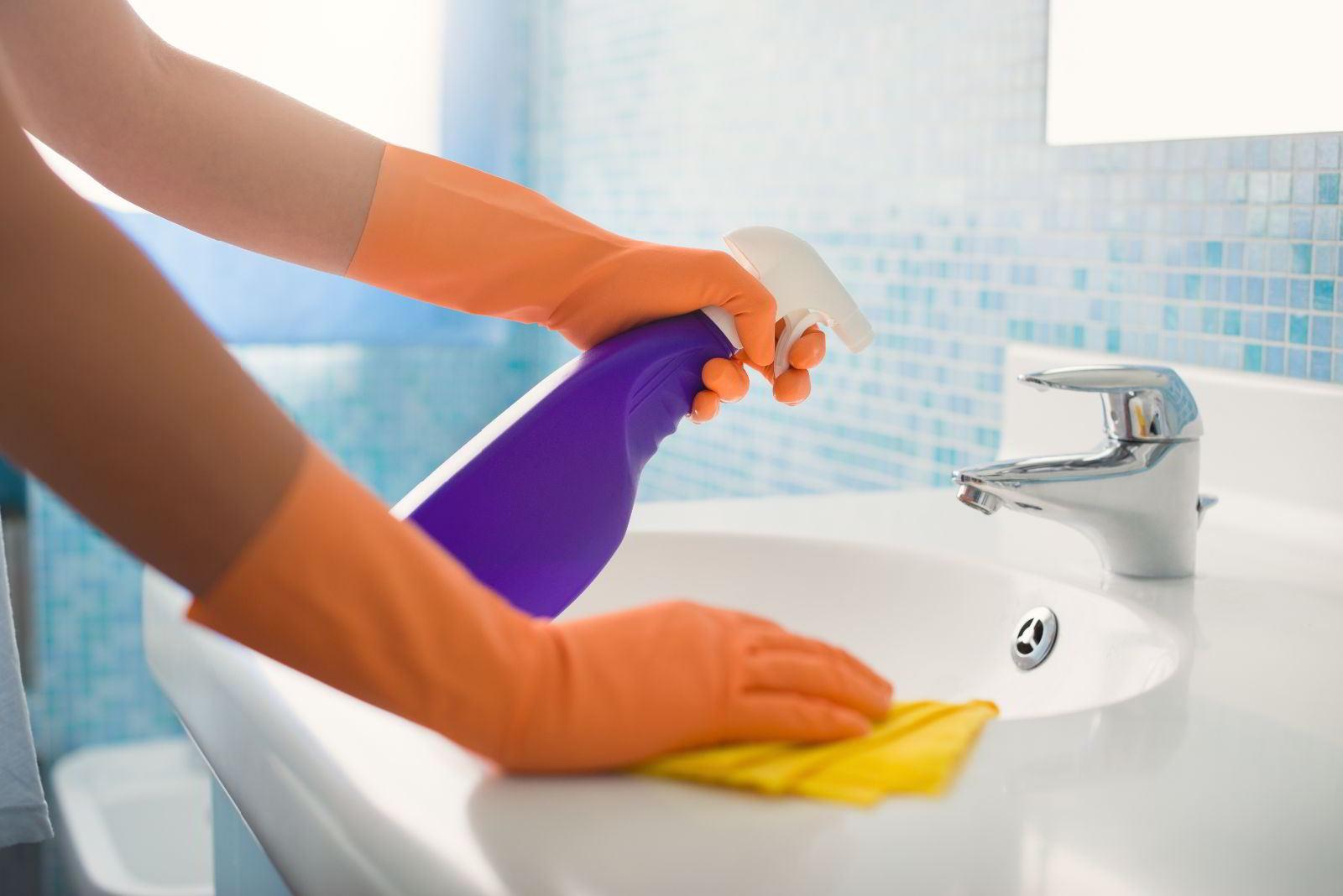 Acercamiento a manos con guantes naranja en un lavamanos limpiando con un trapo y una botella