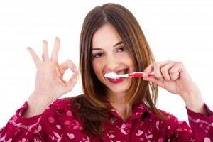 Mujer en camisa roja cepillandose los dientes