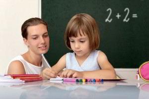 Masstra con una niña sentada escribiendo al fondo un pizarrón