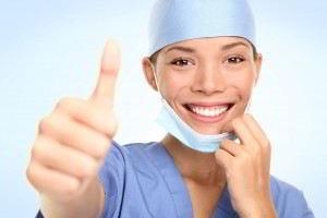 Doctora con traje azul mostrando mano con el dedo pulgar hacia arriba