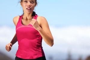 Mujer corriendo con camisa rosa mexicano pantalones negros ajustados en la calle