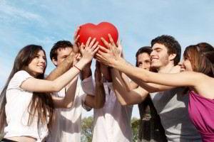 Jóvenes reunidos uniendo sus manos en un corazón
