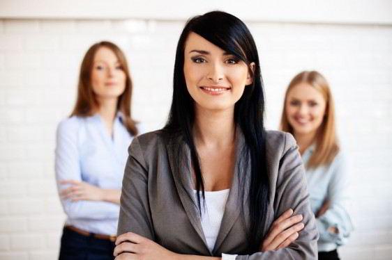 Mujer con traje sastre gris cruzada de brazos en el fondo dos mujeres observandola