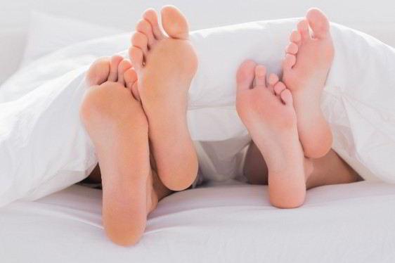 Planta de los pies de un hombre y de una mujer sobresaliendo abajo de unas sabanas