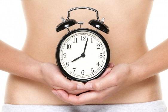 Mujer sosteniendo reloj en el estomago