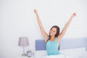 Mujer en la cama estirando brazos al lado de un reloj