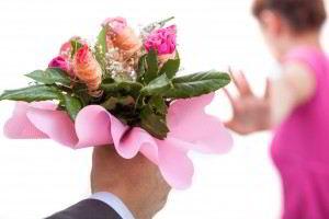 Mano de un hombre con rosas y una mujer vestida de rosa con la mano en alto en señal de rechazo