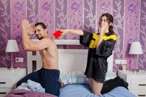 hombre y mujer en una cama ella con tarjera roja señalando hacia afuera