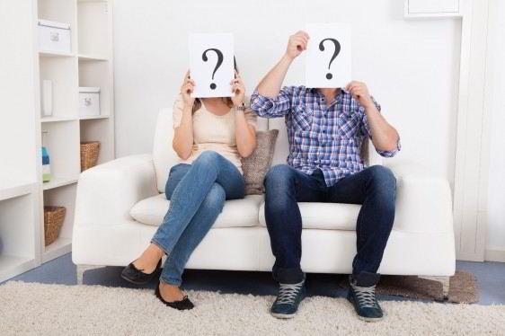 Pareja sentada en un sofa cada uno sosteniendo una hoja con signo de interrogación