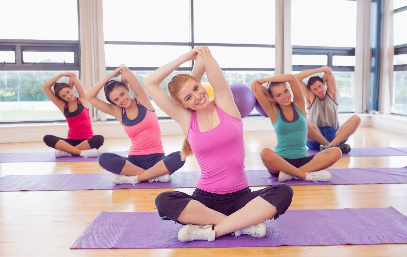 Mujeres haciendo ejercicio en un salón con piso de madera