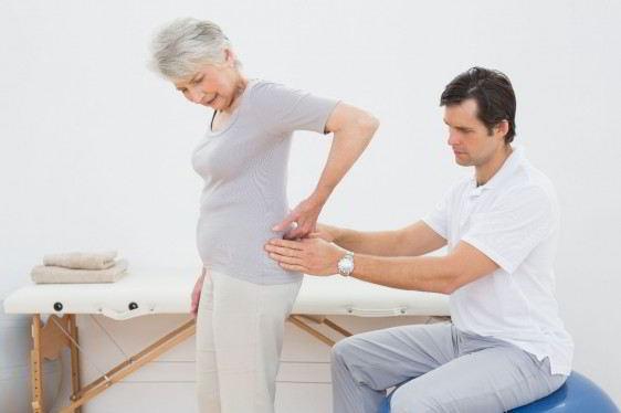 Mujer adulta mayor de pie siendo revisada en la espalda por un hombre