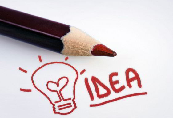 Lápiz rojo sobre una hoja blanca en la hos escrita la palabra idea y un foco con filamento en forma de corazón