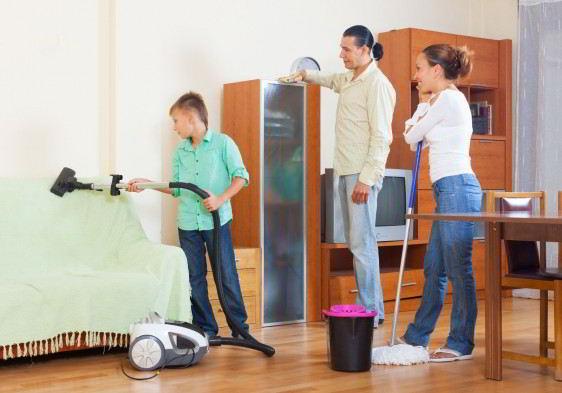 Niño aspirando hombre quitando polvo y mujer trapeando en imagen de concepto de labores domésticas