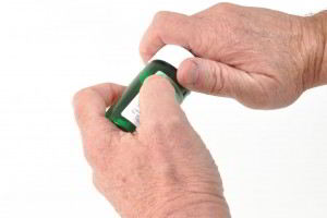 Mano de persona con artitis tratando de abrir boteea verde