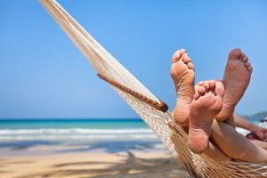Acercamiento de los pies de una pareja en una amaca en la playa