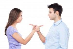 Una mujer señalando a un hombre, el hombre señalando a la mujer