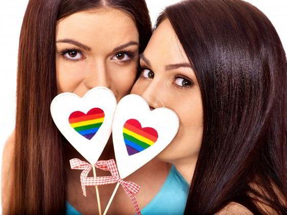 Retrato de dos mujeres cada una phylogeneticcon una paleta de corazón con el arcoiris