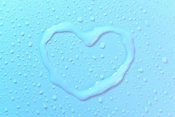Un corazón dibujado con agua sobre una superficie azul