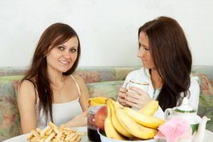 Two smiling women have tea