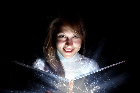 Nila abriendo un libro que emite una luz