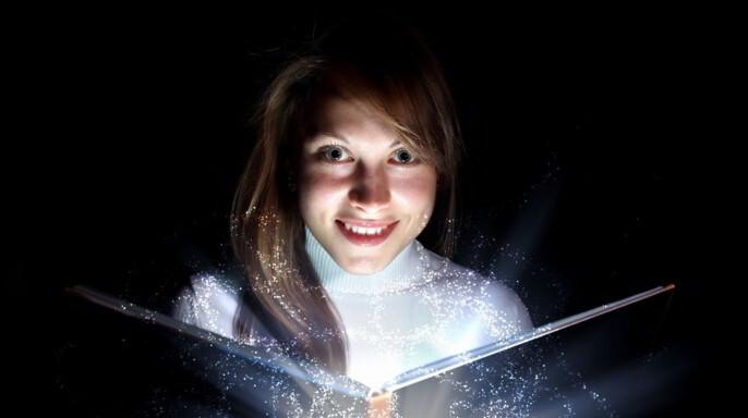 Niña abriendo un libro que emite una luz