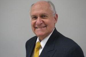 Acercamiento al rostro de Manuel Elkin Patarroyo con saco azul y corbata amarilla en fondo blanco