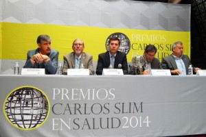 Ganadores del Premio en Salud 2014 sentados en una mesa con mantel que tiene los logotipos de Premios Carlos Slim en Salud 2014