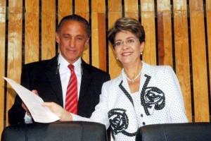 Mercedes Juan entregando un papel a Jorge Arturo Cardona Pérez atras una pared de madera