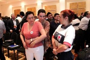 Dos mujeres demostrando la ,aniobra de Heimlich con una persona de cruz roja mexicana al lado al fondo personas haciendo el mismo ejercicio