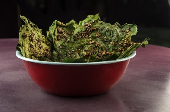 Plato rojo de sopa con una ensalada en su interior en el fondo una mesa volor vino