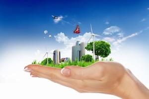 Mano de una mujer sostiene un paisaje de una ciudad con energia eólica, foto celdas y edificios atrás un cielo azul