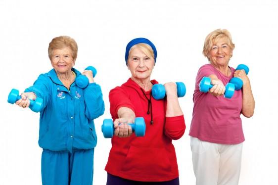 Tres mujeres adultas mayores con ropa deportiva levantando pesas