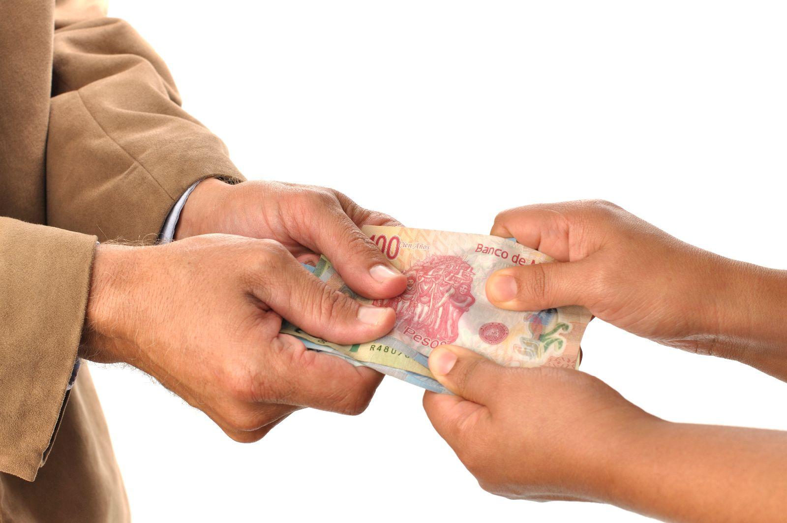 dos personas con las manos en un mismo billete de dinero