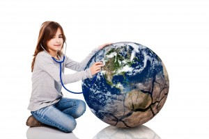 Niña sentada en el piso esuchando un estetoscopio que aplica a una pelota en forma del planeta tierra