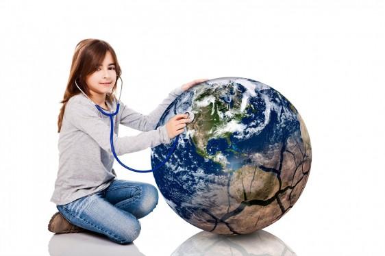 Niña sentada en l piso esuchando un estetoscopio que aplica a una pelota en forma del planeta tierra