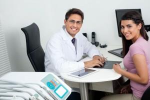 Dentista y paciente sonriendo en consultorio