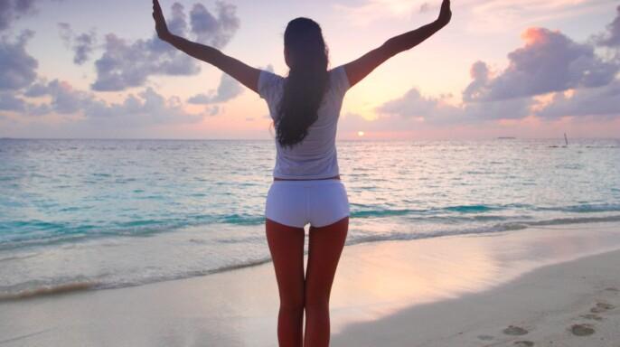 Una mujer con los brazos abiertos en una playa al amanecer