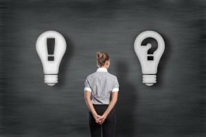 Mujer enfrente de un signo de admiración y otro de pregunta