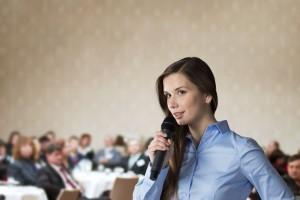 Mujer con camisa azul y microfono en mano al fondo un salón con personas desenfocadas