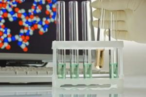 tubos de ensayo y un monitor con una molecula al fondo