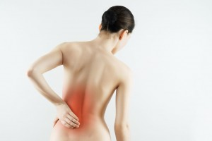 Mujer de espaldas tocandose la espalda baja marcada en tonaildad roja
