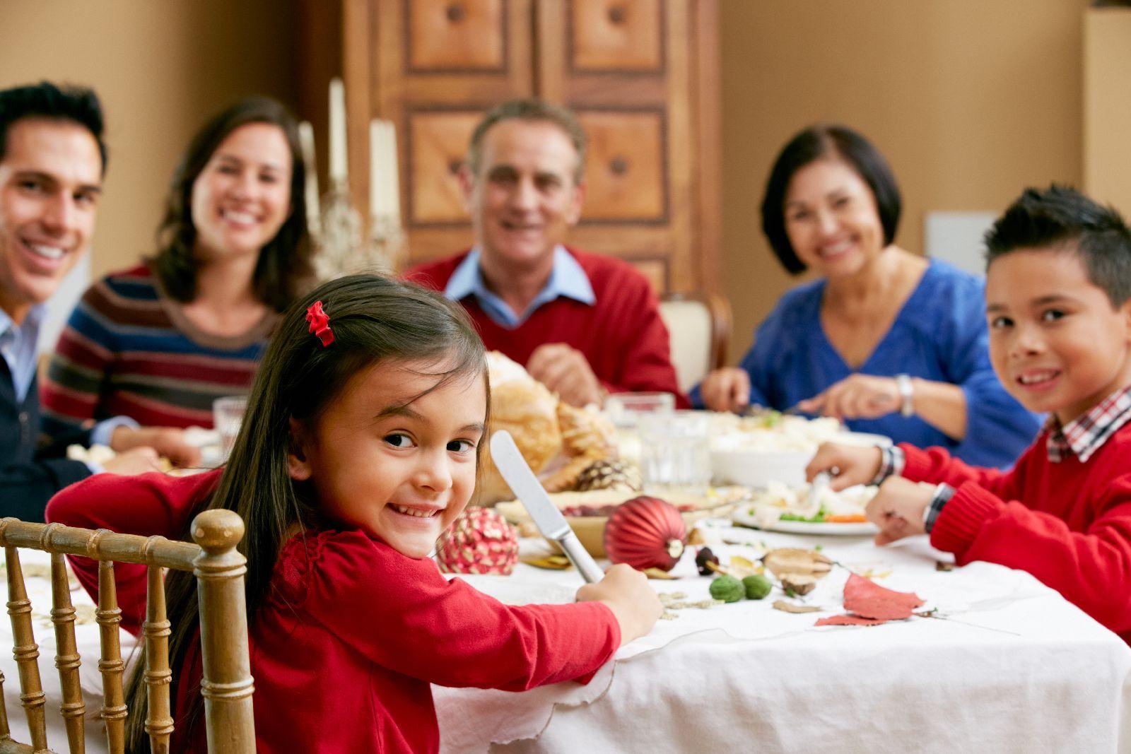 Acercamiento a niña sentada en la mesa sonriendo al fondo desenfocados nilo y adultos en la mesa comiendo