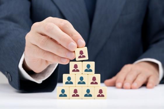 Acercamiento a manos de una persona acomodando dados en forma de piramide, los dados tienen imagen de hombre y mujer